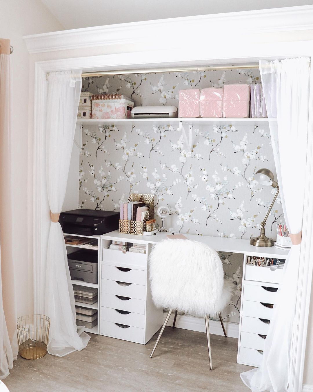 A cloffice with flowery wallpaper and white curtains