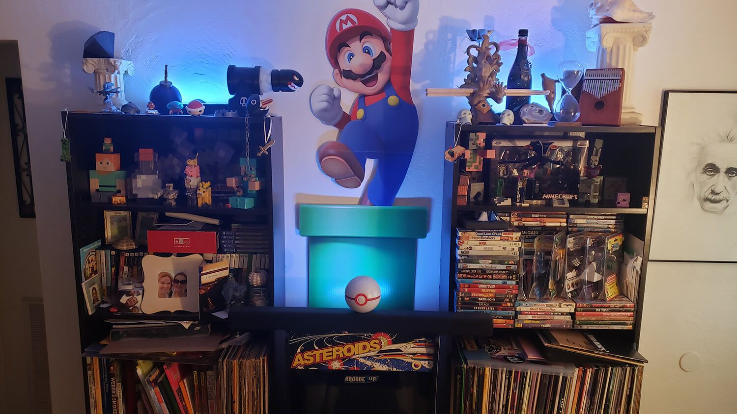 Across the room are a 1UP Asteroids arcade cabinet and bookshelves full of curiosities and collectables